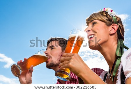Couple on mountain hut in the Alps drinking wheat beer - stock photo
