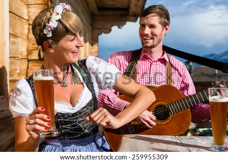 Couple on mountain hut in the Alps making guitar music and drinking wheat beer - stock photo