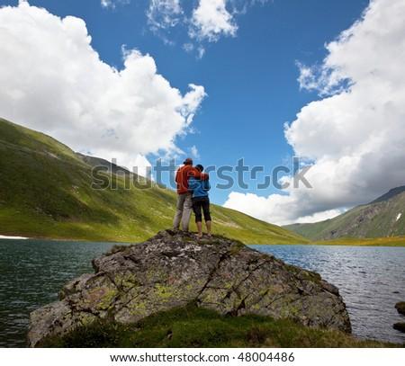 Couple on mountains lake - stock photo