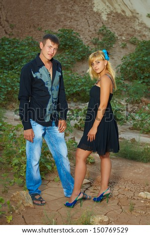Couple on nature in black and blue clothes   looking at camera