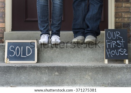couple on new home doorstep with sold sign and first house sign - stock photo