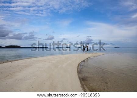 Couple on remote tropical beach, Karimunjawa, Indonesia. Tropical beach, white sand, blue sky's - stock photo