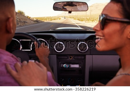 Couple On Road Trip Driving In Convertible Car - stock photo
