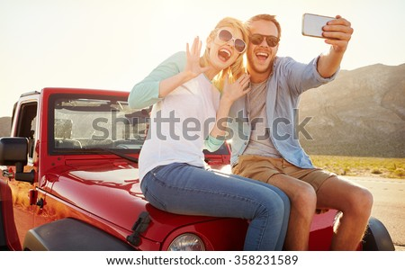 Couple On Road Trip Sit On Convertible Car Taking Selfie - stock photo
