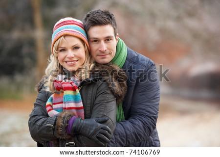 Couple On Romantic Winter Walk Through Frosty Landscape - stock photo