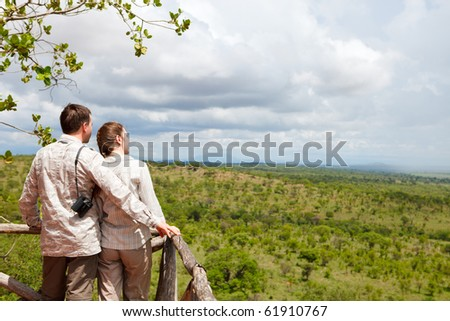 Couple on safari vacation looking to savanna from balcony - stock photo