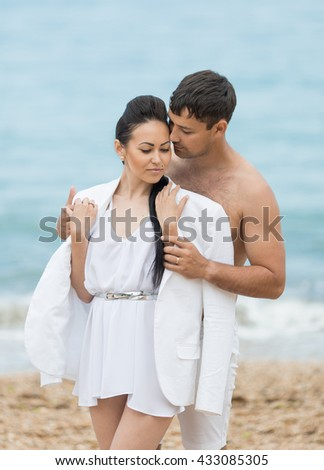 Couple on seashore in cloudy day. Young man offer jacket his girlfriend - stock photo