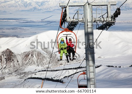 Couple on ski elevator in winter mountains