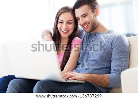 Couple on sofa with laptop - stock photo