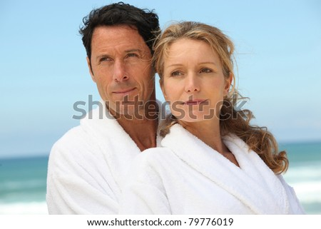 Couple on the beach in white dressing downs - stock photo