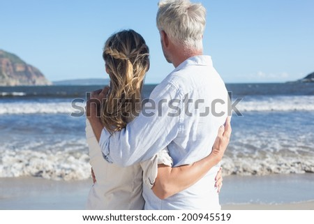 Couple on the beach looking out to sea on a sunny day - stock photo