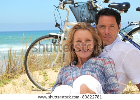 couple on the beach with bikes - stock photo