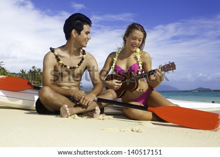 couple on the beach with their surf skis playing ukulele