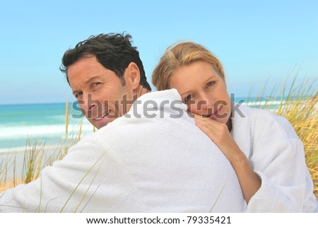 Couple on the dunes in towelling robes - stock photo
