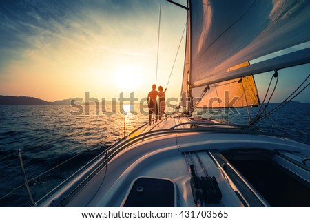 Couple on the sailing boat at sunset