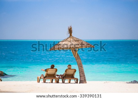 Couple on the sun beds under umbrella
