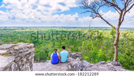 Couple on the top of Coba pyramid watching the mexican jungle - stock photo