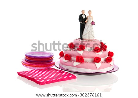 Couple on top of pink wedding cake with red roses isolated over white background - stock photo