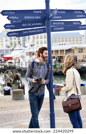 couple on travel holiday at sign with guide book - stock photo