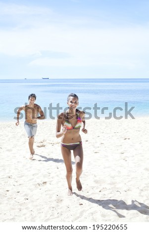 couple on vacation running on the beach in Boracay in the Philippines