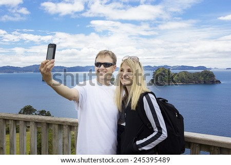 Couple on vacation taking photo of beautiful ocean view - stock photo