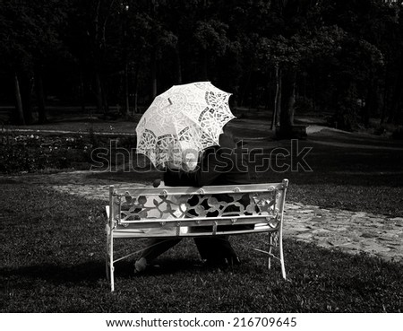 Couple on wedding day in vintage photo, man and woman sitting in the park in sepia photo, groom and bride on wedding day sitting in the park, couple under umbrella - stock photo