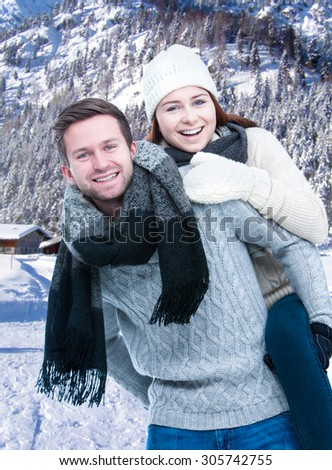 Couple on winter vacation, young man piggybacking his girlfriend - stock photo