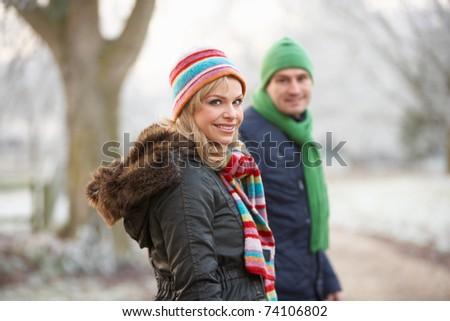 Couple On Winter Walk Through Frosty Landscape - stock photo