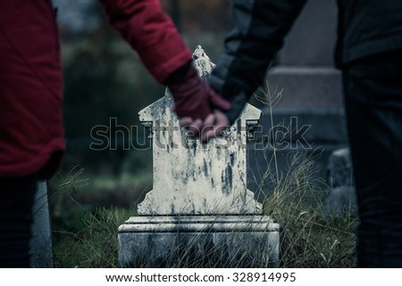 Couple or Brother and Sister Holding Hands in front of a small Gravestone. Lost of a Loved one is never easy. - stock photo
