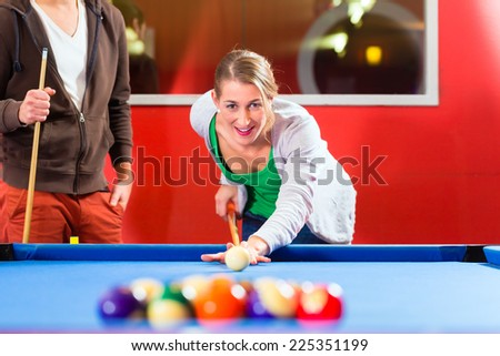 Couple or friends playing billiard with cue and balls on pool table  - stock photo