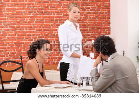 Couple ordering a wine in a restaurant - stock photo