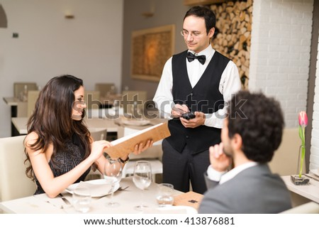 Couple ordering dinner in a luxury restaurant - stock photo