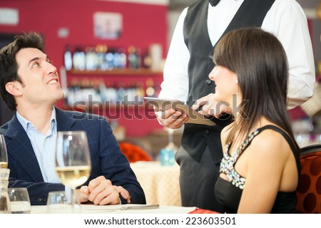 Couple ordering food in a restaurant - stock photo