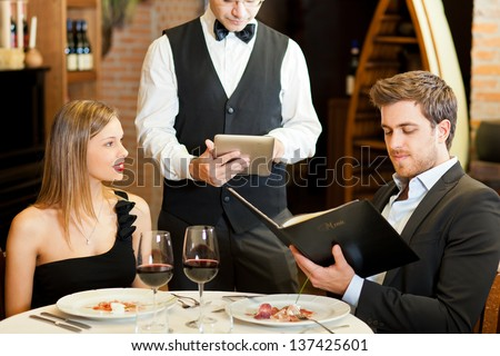 Couple ordering meal at restaurant - stock photo