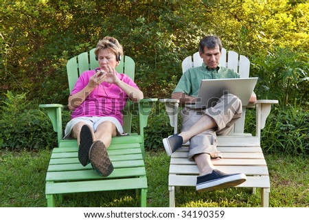 Couple outdoors relaxing...each busy with his own technology (laptop and MP3). Some motion blur. - stock photo