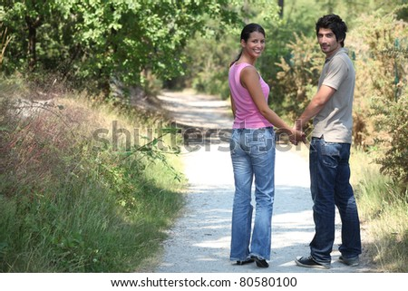 Couple outdoors walking hand in hand - stock photo