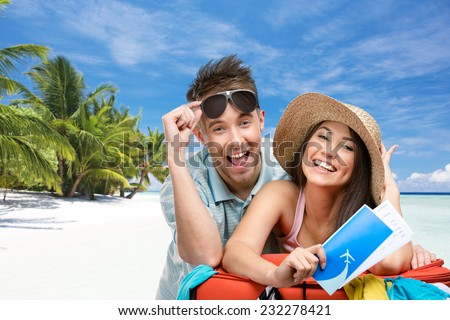 Couple packs up suitcase with clothing for honeymoon trip, tropical beach background. Concept of romantic vacations and lovely honeymoon - stock photo