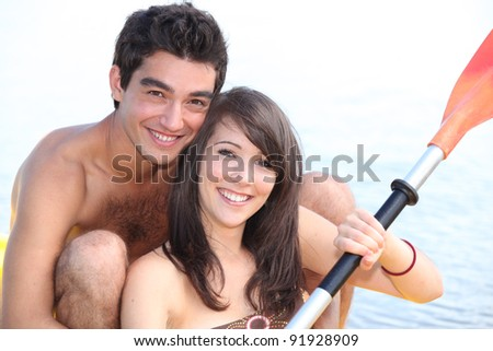 Couple paddling in boat - stock photo