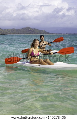 couple paddling surf skis in hawaii - stock photo
