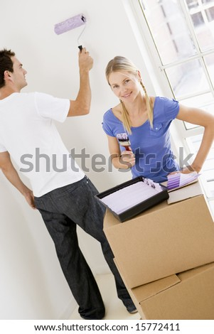 Couple painting room in new home smiling - stock photo