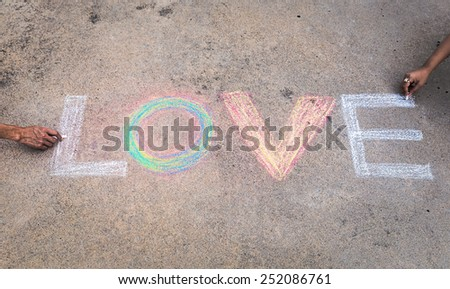 Couple painting the word 'love' with sweet and romantic-toned effect. - stock photo