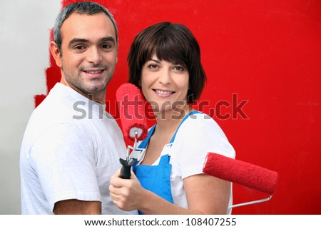 Couple painting wall with roller - stock photo