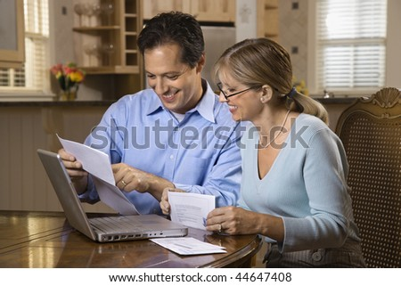 Couple paying bills online with laptop computer at home. - stock photo