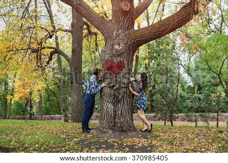 Couple peeking around opposite sides of tree. Concept of love story and dating. - stock photo