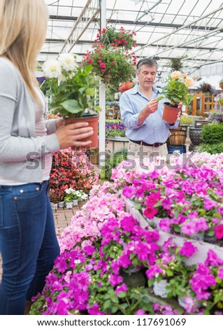 Couple picking out plants in garden center