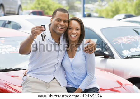 Couple picking up new car from lot - stock photo