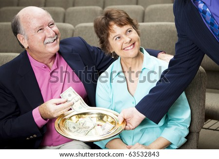 Couple placing money in a church collection plate. - stock photo