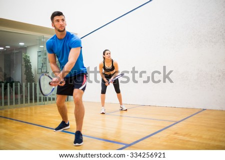 Couple play some squash together in the squash court - stock photo