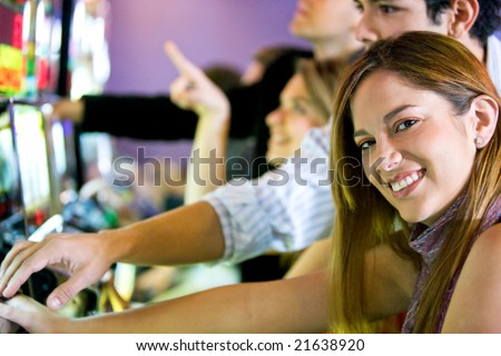 couple playing at the slot machines in a casino - stock photo