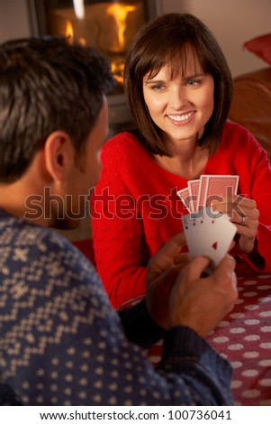 Couple Playing Cards By Cosy Log Fire - stock photo